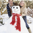 Teenage Couple Building Snowman - Stockfoto