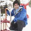 Teenage Boy With Sledge Next To Snowman — Stock Photo
