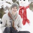 Teenage Boy With Sledge Next To Snowman - Stock Photo