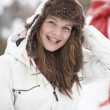 Teenage Girl Wearing Winter Clothes In Snowy Landscape - Stock Photo