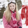 Teenage Girl With Sledge Next To Snowman — Photo