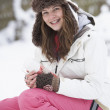 Teenage Girl Sitting On Sledge With Flask And Hot Drink - Stock Photo