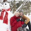 Teenage Couple In Winter Landscape Next To Snowman With Flask An — Stock Photo