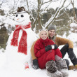 Teenage Couple In Winter Landscape Next To Snowman With Flask An - Stock Photo