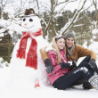 Teenage Couple In Winter Landscape Next To Snowman With Flask An — Stock Photo #4837346