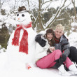 Teenage Couple In Winter Landscape Next To Snowman With Flask An — Stock Photo #4837347