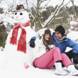Teenage Couple In Winter Landscape Next To Snowman With Flask An - Stock fotografie
