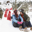 Teenage Couple In Winter Landscape Next To Snowman With Flask An - Foto Stock