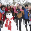 Group Of Teenage Friends Building Snowman In Garden - Stock fotografie