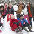 Group Of Teenage Friends Building Snowman In Garden - Foto Stock
