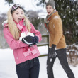 Teenage Couple Having Snowball Fight In Snowy Landscape - Stock fotografie