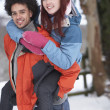 Teenage Boy Giving Girl Piggyback In Snowy Landscape — Stock Photo #4837360
