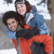 Teenage Boy Giving Girl Piggyback In Snowy Landscape — Stock Photo