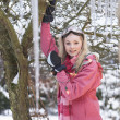 teenage girl hanging fairy lights in tree with icicles in foregr — Stock Photo