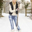 Foto Stock: Teenage Girl Clearing Snow From Drive