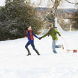 Teenage Couple Pulling Sledge Across Snowy Field - 图库照片