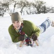 Young Man Riding On Sledge In Snowy Landscape - Stock fotografie