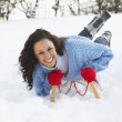 Young Woman Riding On Sledge In Snowy Landscape - Stock fotografie