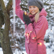 Teenage Girl Hanging Fairy Lights In Tree With Icicles In Foregr - Stockfoto