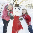 Young Girl With Grandmother Building Snowman In Garden — Stock Photo
