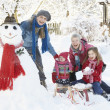 Young Girl With Grandmother And Mother Building Snowman In Garde - Stock fotografie