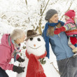 Young Girl With Grandmother And Mother Building Snowman In Garde - Stock Photo