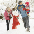 Young Girl With Grandmother And Mother Building Snowman In Garde — Stock Photo