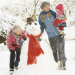 Young Girl With Grandmother And Mother Building Snowman In Garde - Stockfoto