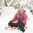 Senior Woman Sitting On Sledge In Snowy Landscape - Stockfoto