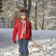 Young Girl Pulling Sledge Through Snowy Landscape - Stockfoto