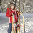 Young Girl Holding Sledge In Snowy Landscape - Stockfoto