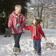 Young Girl With Grandmother Pulling Sledge Through Snowy Landsca - Stok fotoraf