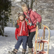 Young Girl With Grandmother Holding Sledge In Snowy Landscape - Stockfoto