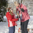 Young Girl Showing Grandmother Icicle In Snowy Landscape - Stockfoto