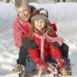 Young Girl With Grandmother Riding On Sledge In Snowy Landscape - Stock fotografie