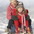 Young Girl With Grandmother Riding On Sledge In Snowy Landscape - Foto Stock