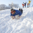 Man Sledging Down Hill With Family Watching - Stock fotografie