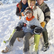 Family Enjoying Sledging Down Snowy Hill — Stock Photo #4837552