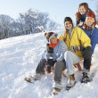 Family Enjoying Sledging Down Snowy Hill - Stock Photo