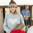 Young Couple Collecting Logs From Wooden Store In Snow — Stock Photo #4837560