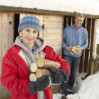Young Couple Collecting Logs From Wooden Store In Snow — Stock Photo