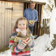 Father And Daughter Collecting Logs From Wooden Store In Snow — Stock Photo
