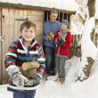 Family Collecting Logs From Wooden Store In Snow — Stock Photo