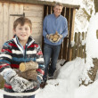 Father And Son Collecting Logs From Wooden Store In Snow — Stock Photo