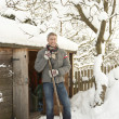 Middle Aged Man Clearing Snow From Path To Wooden Store - Stock fotografie