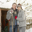 Foto Stock: Young Couple Clearing Snow From Path To Wooden Store
