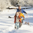 Father And Children Pulling Sledge Up Snowy Hill — Stock Photo #4837570