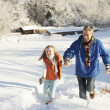Father And Daughter Pulling Sledge Up Snowy Hill — Stock Photo