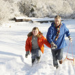 Father And Son Pulling Sledge Up Snowy Hill — Stock Photo