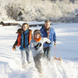 Father And Children Pulling Sledge Up Snowy Hill — Stock Photo